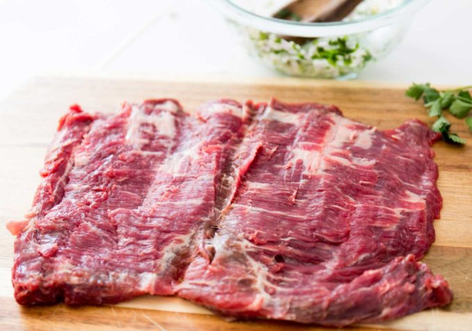 Butterflied flank steak on cutting board