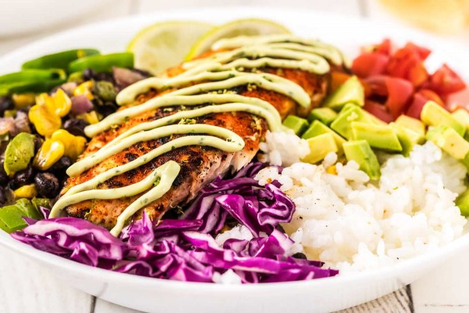 These fresh and healthy fish taco bowls are filled with blackened white fish, corn and black bean salsa, and topped with cilantro avocado crema! On the table in about 30 minutes for a quick and easy dinner idea! #fishtacos #fish #tacos #blackened #bowls #mexican #dinner #healthyrecipe #healthy #seafood