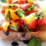 The Chunky Chef | Classic bruschetta gets a gourmet twist by using sweet heirloom tomatoes, basil, fresh mozzarella, and drizzled with a decadent balsamic reduction glaze!