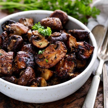 White bowl of roasted mushrooms with silverware