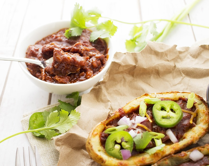 Loaded Beef BBQ Potato Skins | The Chunky Chef | The classic potato skins appetizer gets a BBQ twist! Savory beef BBQ on top of crispy and cheesy potato skins - perfect for game day or a great snack!