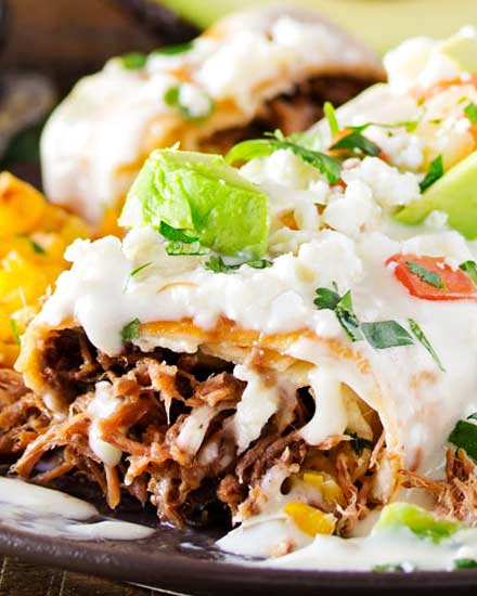 Tortillas stuffed with tender, spicy, slow cooked spiced beef (barbacoa-style), fried to crunchy perfection, then smothered in a velvety smooth white queso! Great meal to use up leftovers too! #beef #chimichangas #mexican #easyrecipe #dinner #barbacoa #queso #cheese #smothered