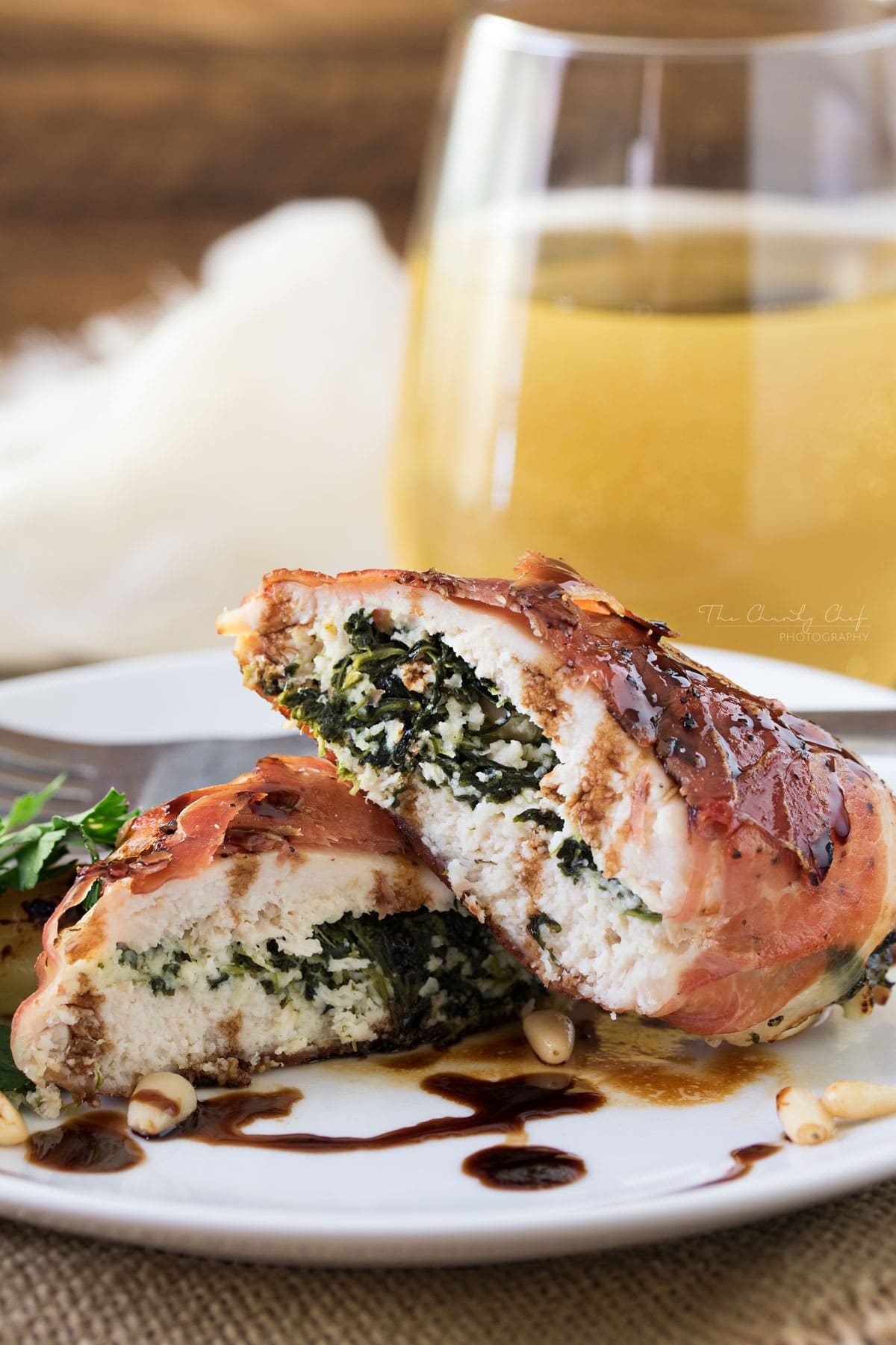 Florentine Stuffed Chicken | This Florentine stuffed chicken is filled with a deliciously cheesy spinach mixture, and toasted pine nuts, then wrapped in prosciutto and baked! | http://thechunkychef.com