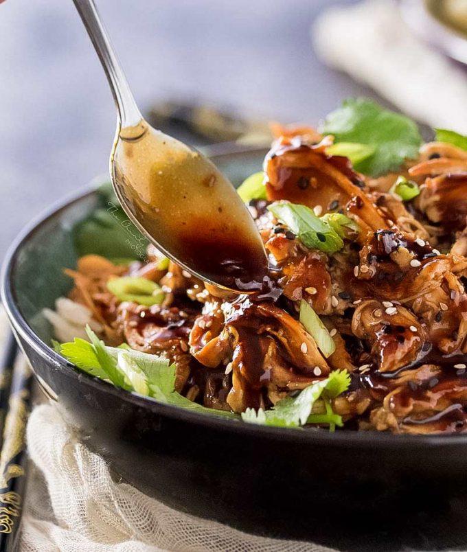 spooning honey garlic sauce over shredded chicken