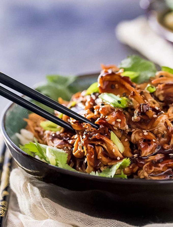 black chopsticks picking up some shredded chicken