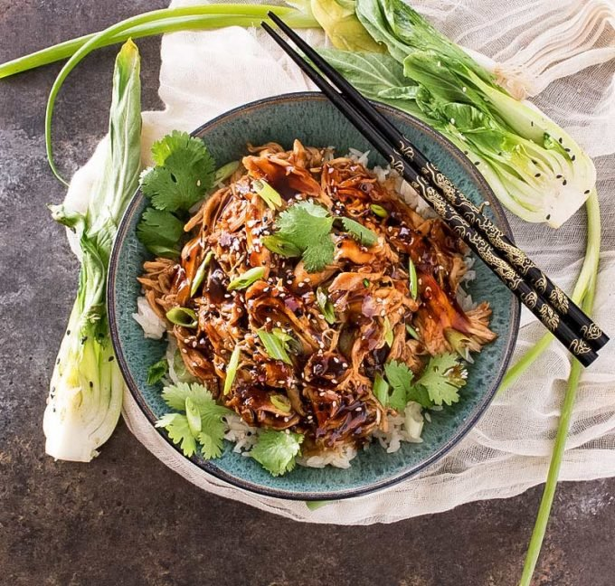 Overhead view of shredded asian chicken in bowl with chopsticks