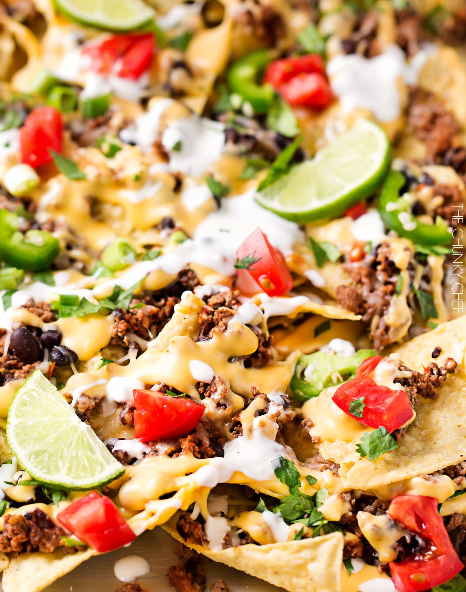Sheet Pan Beef and Black Bean Nachos | These sheet pan nachos are sure to be a crowd pleaser! Layer after layer of mouthwatering flavor, smothered with a jalapeño cheese sauce and loaded with classic nacho toppings! | http://thechunkychef.com