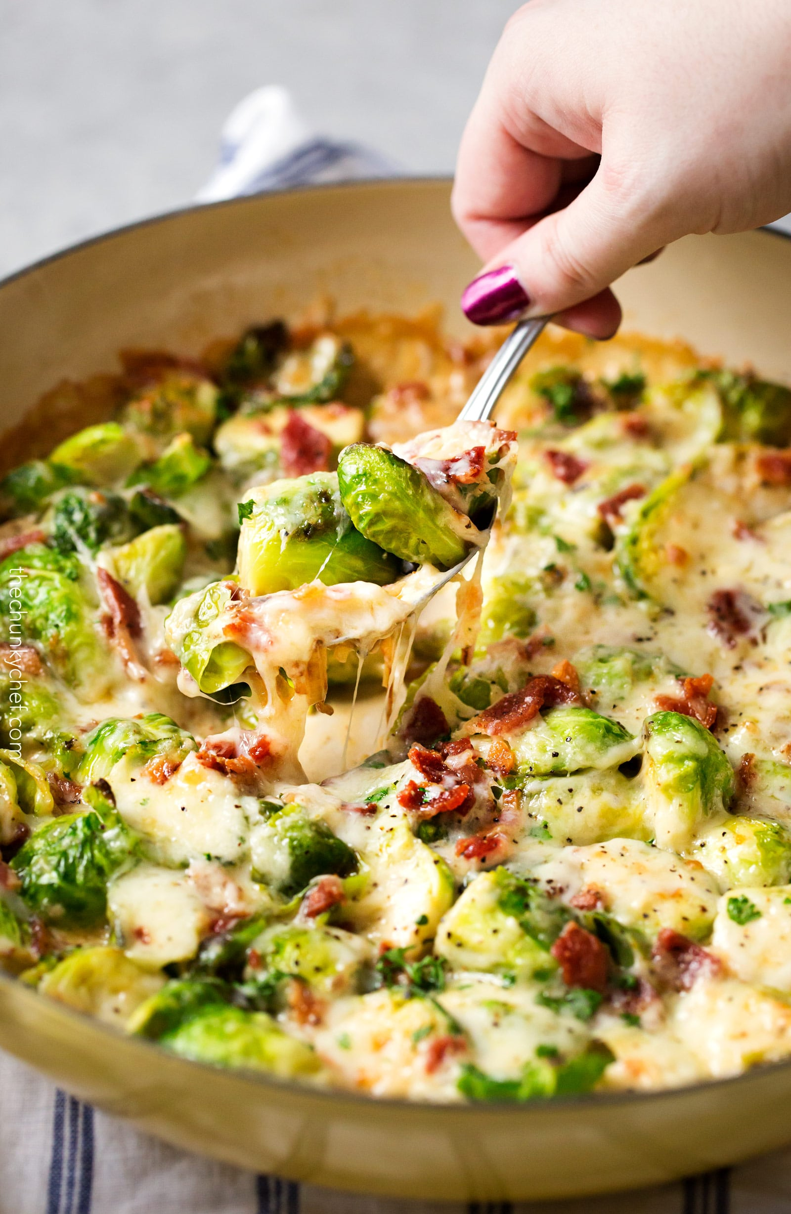 Cheesy Brussels Sprouts with Bacon | These Brussels sprouts are sautéed with shallots and garlic, topped with cream, two types of cheese, sprinkled with bacon, and baked until bubbly. It will convert even the most die hard Brussels sprouts haters! | http://thechunkychef.com