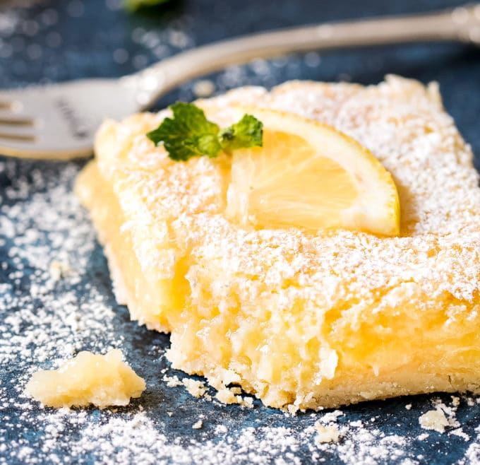 The best Creamy Lemon Bars have an easy shortbread crust and a layer of thick and creamy lemon filling. Perfectly tangy and sweet - such a classic dessert recipe that anyone can make! #lemonbars #lemonsquares #lemon #citrus #bars #dessert #baking #dessertrecipe #easyrecipe #spring