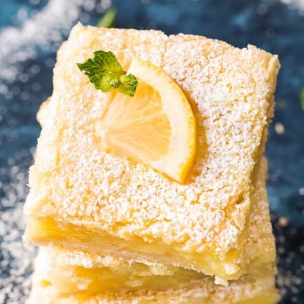 Lemon bars with lemon slice on top with powdered sugar