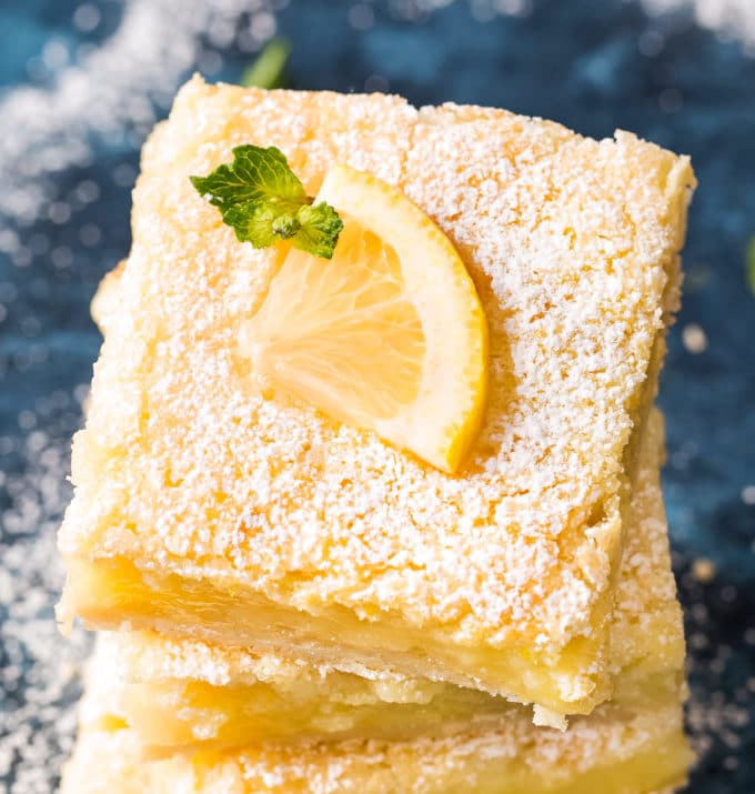Lemon bars with lemon slice on top with powdered sugar