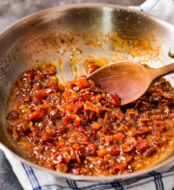 stirring bacon jam in a stainless steel skillet