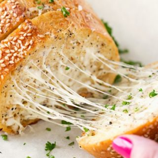 Homemade Garlic Bread | Who knew homemade garlic bread could be so easy!  Start off with your favorite bakery bread, add a mouthwatering garlic parmesan and herb spread, extra cheese if you want, and bake until warm, gooey, buttery and toasty! | http://thechunkychef.com