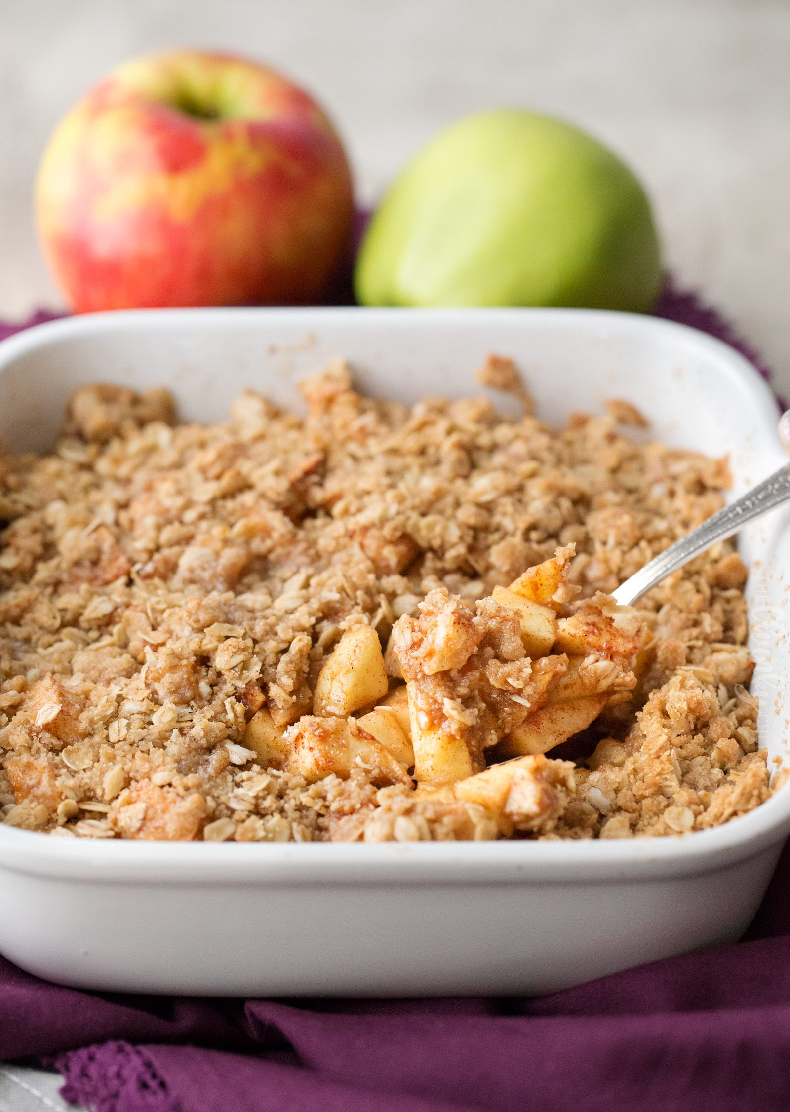 Picture of a spoon scooping some apple crisp out of the baking dish.