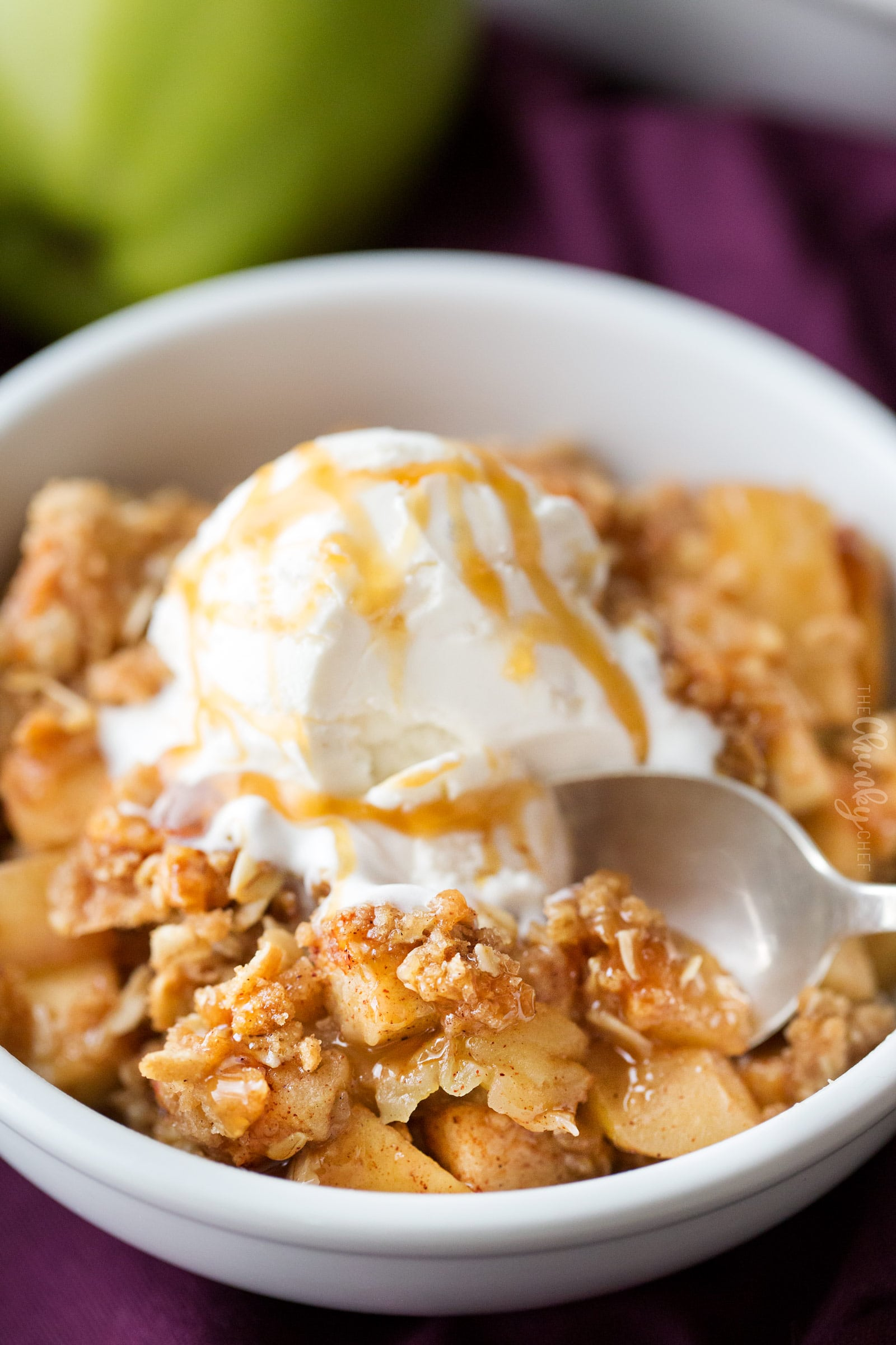 Apple crisp in a bowl with scoop of vanilla ice cream and caramel sauce, with a spoon taking a scoop