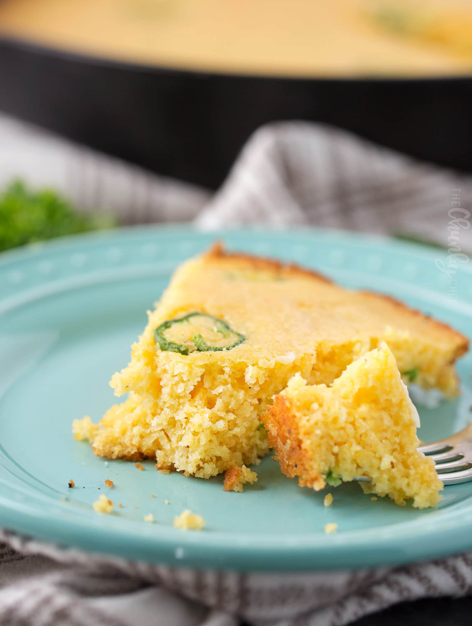 Homemade cornbread slice on blue plate with a forkful missing