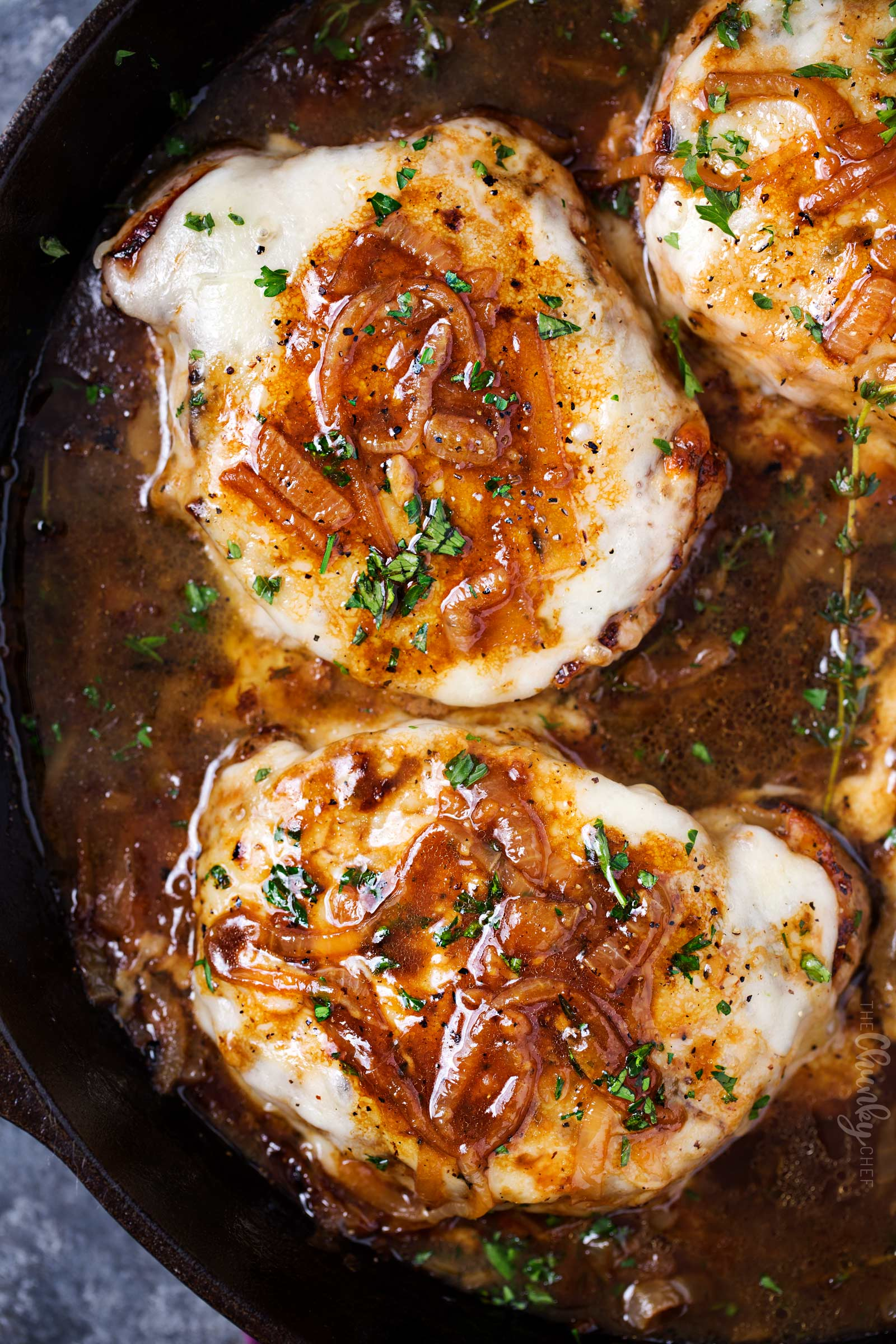 Overheat view of smothered pork chops in skillet