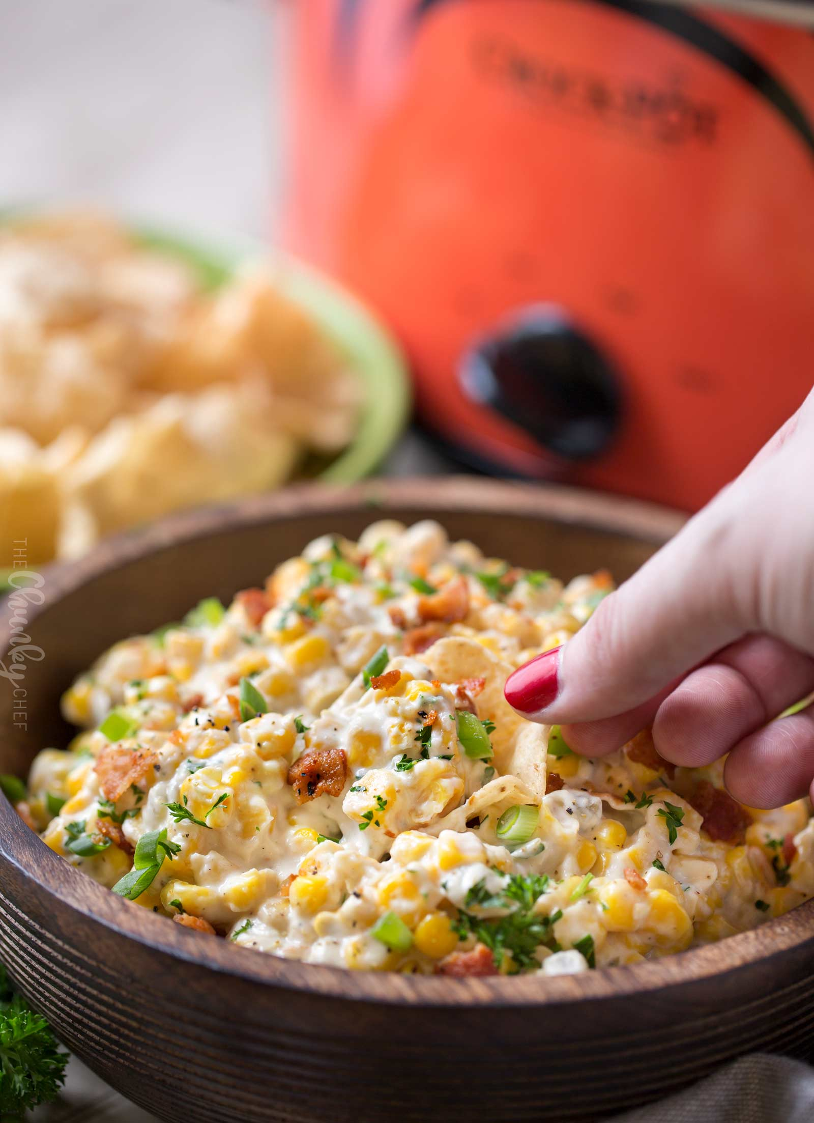 Chip scooping corn dip from wooden bowl