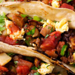 Chorizo and Potato Breakfast Tacos | Charred soft tortillas loaded with spicy chorizo, crispy potatoes, scrambled eggs and smothered in homemade salsa.  The BEST way to start off your day! | The Chunky Chef | #tacos #breakfast #chorizo #potato #eggs #breakfastrecipes