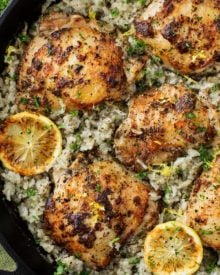 Marinated Greek lemon chicken thighs are seared then baked on top of a lemon and herb flavored rice.  The easiest one pan meal that the whole family will love!