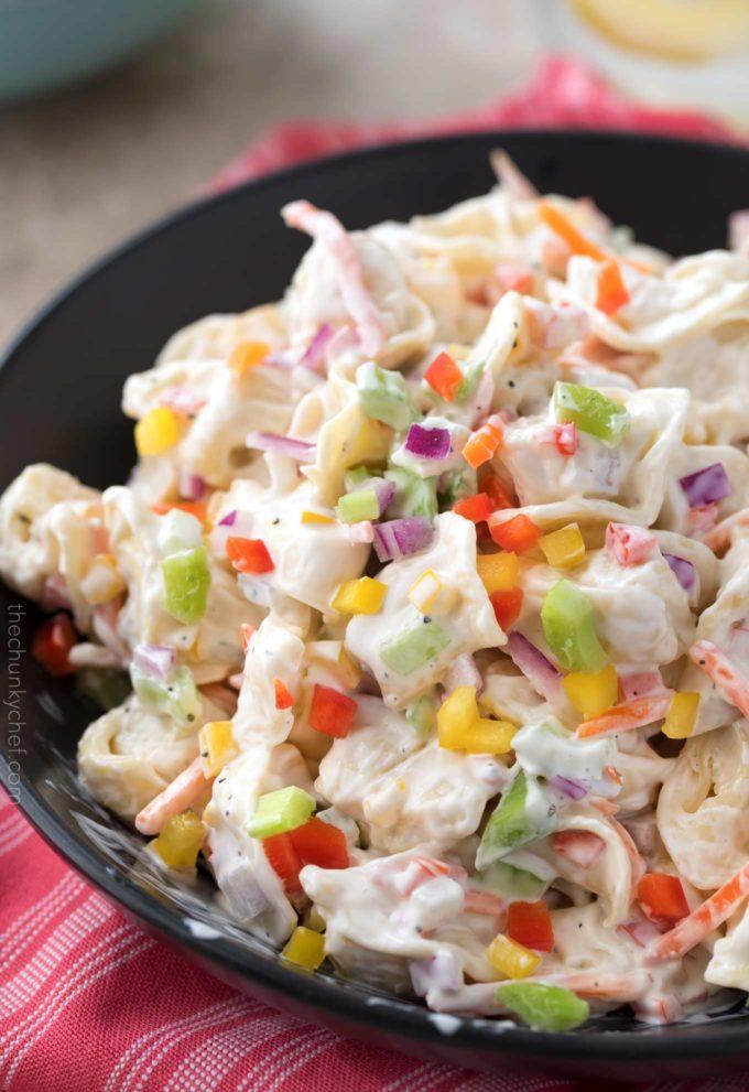 Brightly colored rainbow tortellini salad in black bowl