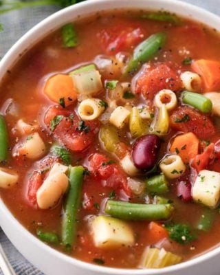 Way better than the soup from that popular Italian restaurant chain, this minestrone soup is bursting with hearty flavors and is made easily in the slow cooker!  Vegetables, beans and pasta are simmered in a rich vegetable broth to make a soul-warming soup. | #minestrone #soup #slowcooker #crockpot #copycat #souprecipe