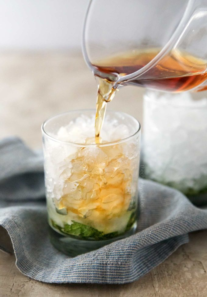 Pouring bourbon into mint julep cocktail