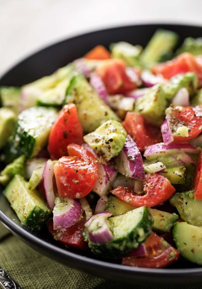 Tomato avocado salad with greek dressing in black bowl