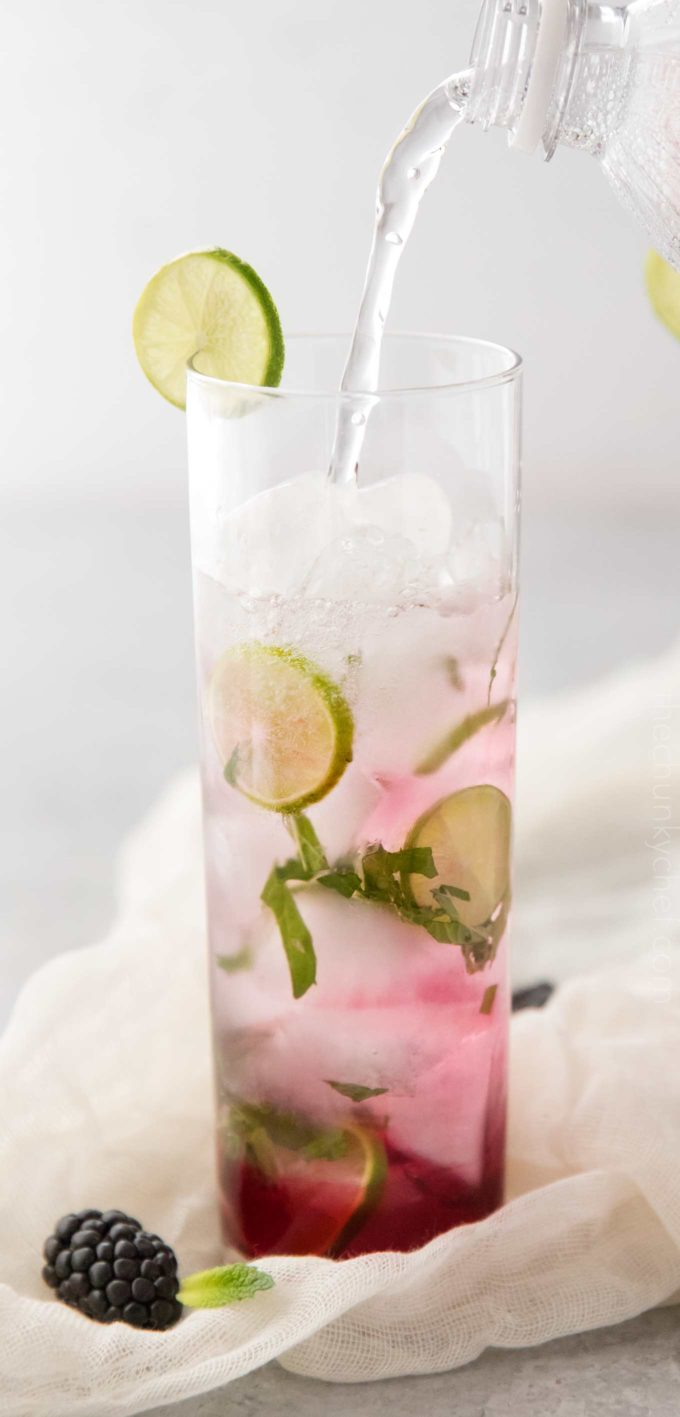 Pouring club soda in blackberry mojito