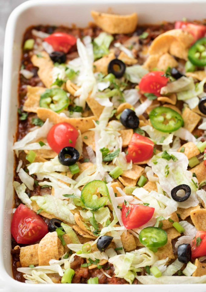 Taco casserole in white baking dish with toppings