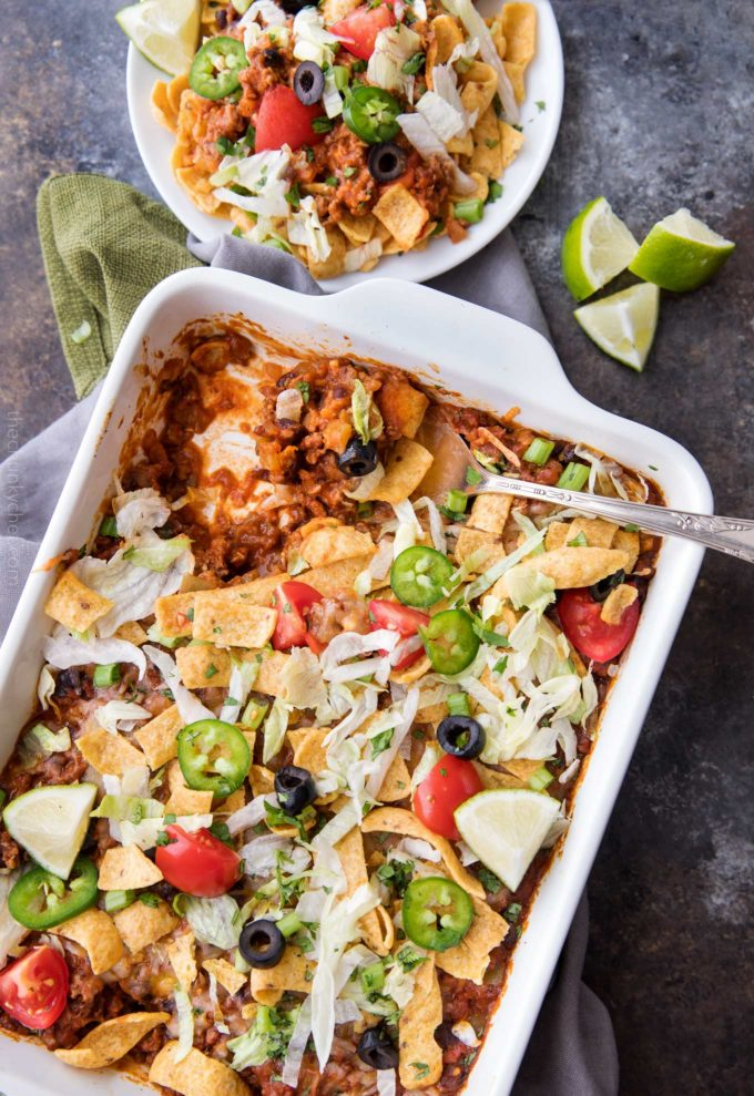 Taco casserole in white baking dish with serving spoon