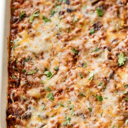 This beef and bean taco casserole is incredibly easy, made from scratch, freezer-friendly, and a huge hit families!  All the flavors of taco night that you love, in a comforting casserole to feed a crowd. #taco #tacocasserole #mexican #freezermeal #casserole #makeahead #tacotuesday