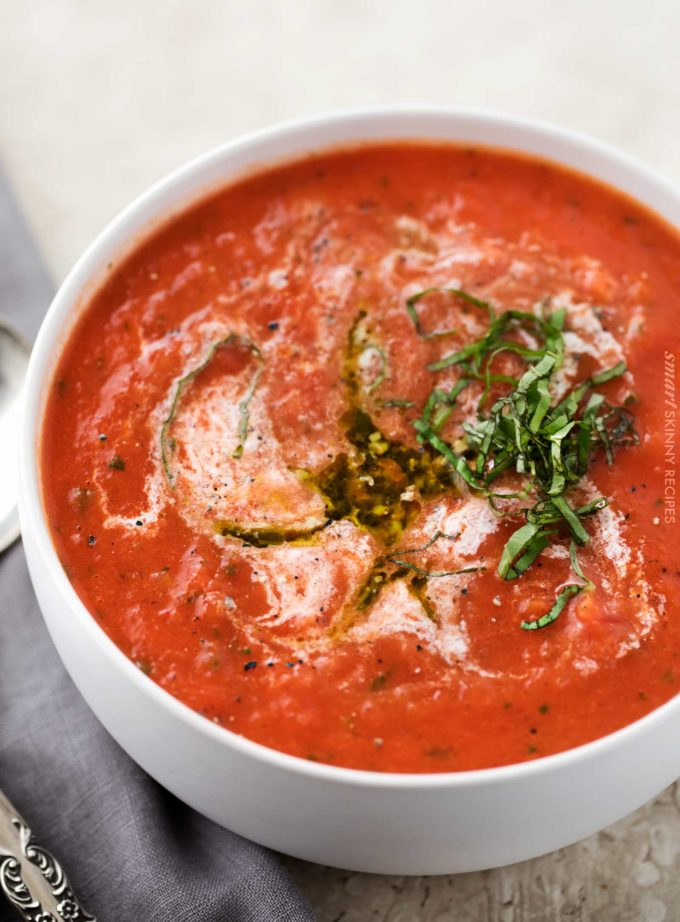Tomato basil soup in white bowl with drizzle of pesto and cream