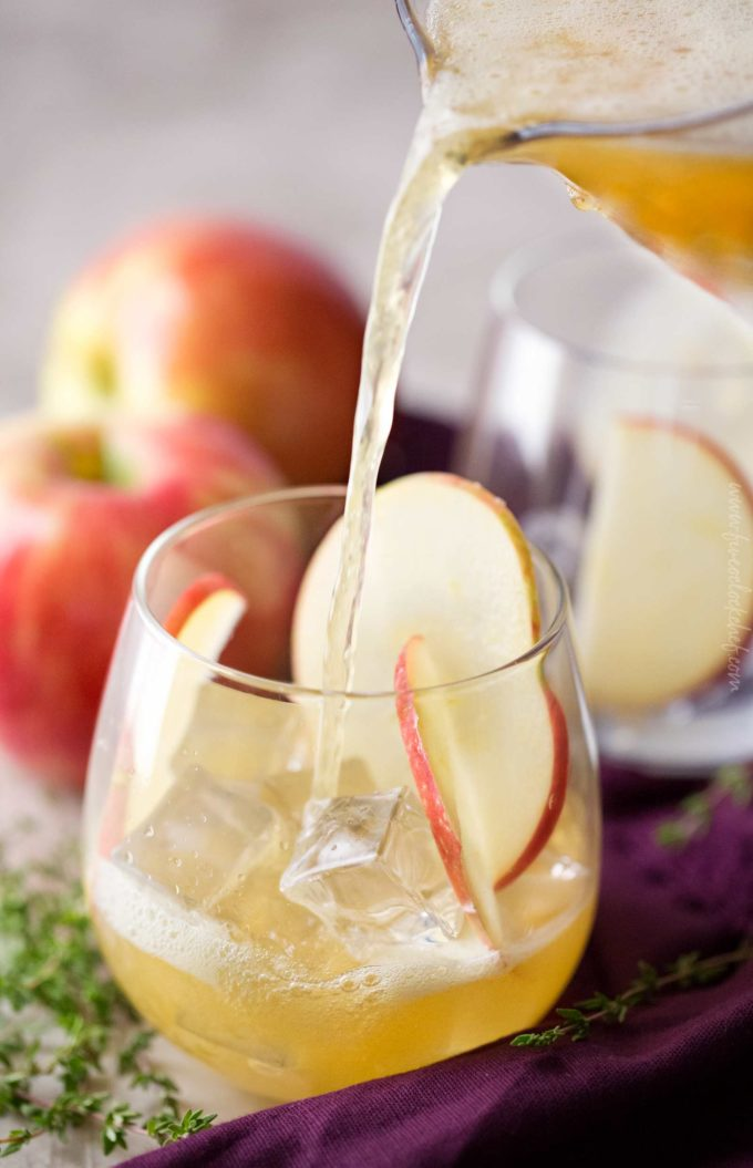 Pouring maple honeycrisp bourbon cocktail into glass