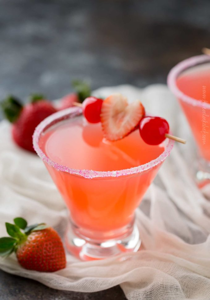 Pink vodka cocktail with strawberry and cherry garnish