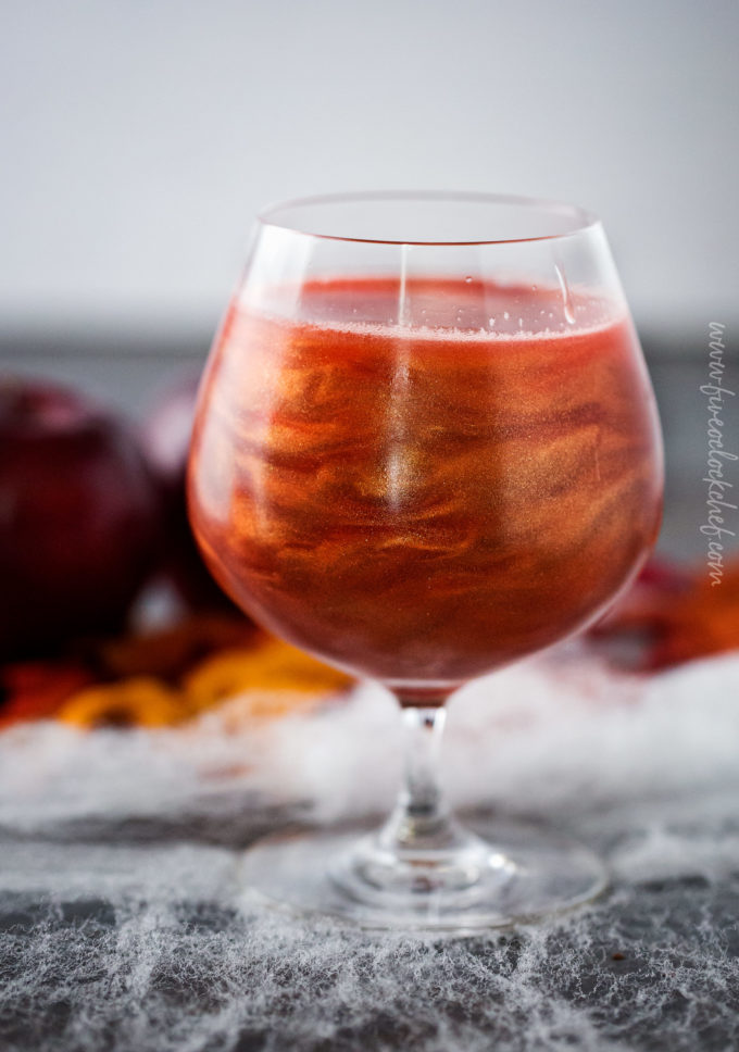 Swirls of luster dust in poisoned apple cider cocktail