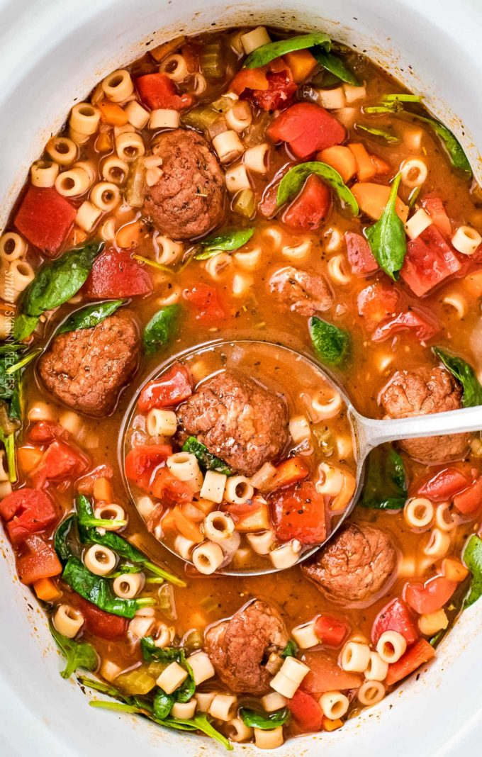 Ladle of Italian meatball soup in slow cooker