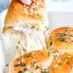 The ultimate party or finger food, these melt in your mouth ham and cheese sliders are made savory with the addition of garlic and herbs, drizzled in a garlic/shallot butter and baked until tender and golden! #appetizer #partyfood #fingerfood #sliders #hamandcheese #garlicandherb #easyrecipe