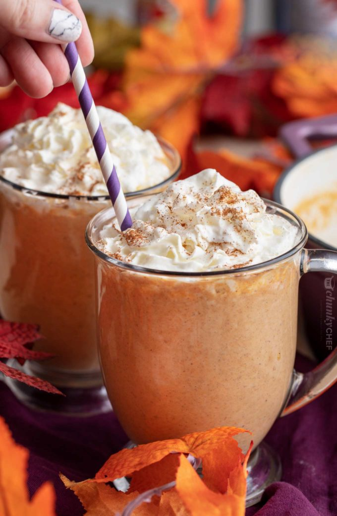Adding a straw to mug of pumpkin hot chocolate