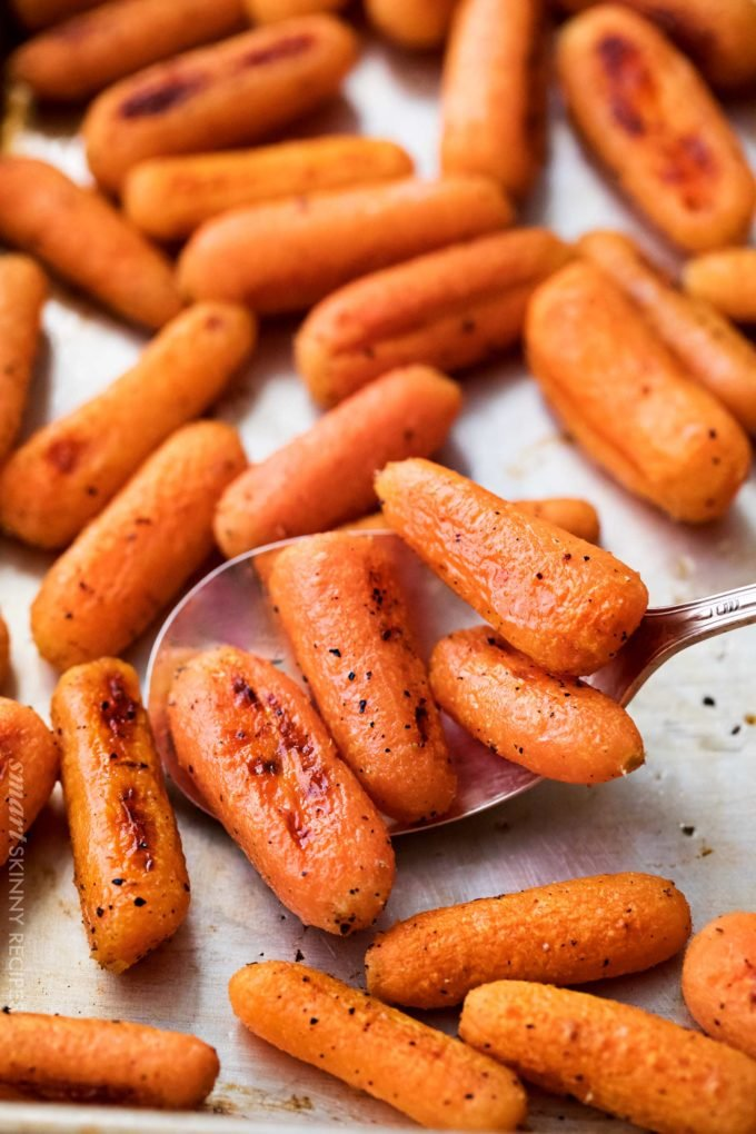Scoop of roasted carrots on sheet pan