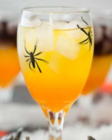 This non-alcoholic Halloween party punch is layered to resemble candy corn, with plastic spiders added for a fun spooky effect! #punch #party #trickortreat #halloween #nonalcoholic #drinkrecipe #mocktail