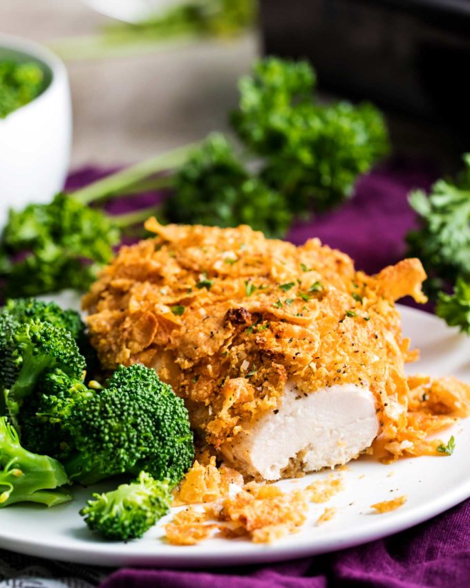 Baked chicken with cornflakes on white plate