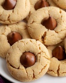 These classic and iconic Peanut Butter Blossoms Cookies are soft and chewy, with a crackly sugary crust and studded with a solid milk chocolate kiss.  Perfect for any holiday, bake sale or cookie exchange! #cookierecipe #cookie #Christmas #baking #peanutbutter #peanutbutterandchocolate #xmas #holidaybaking #holiday