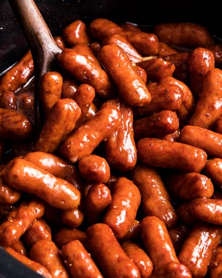 Always a crowd-pleaser, these Crockpot Little Smokies are slow cooked in a sauce made with beer, garlic, honey, brown sugar and bbq sauce.  Perfect for game day, holidays, or any party! #littlesmokies #lilsmokies #partyfood #appetizer #recipe #easyrecipe #crockpot #slowcooker