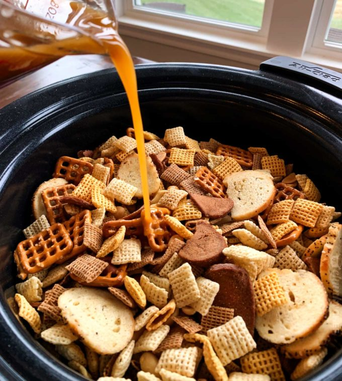 Pouring seasoned butter over chex mix in slow cooker