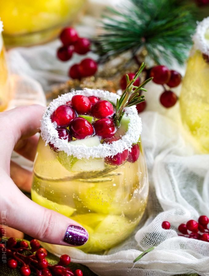Holding a glass of christmas sangria