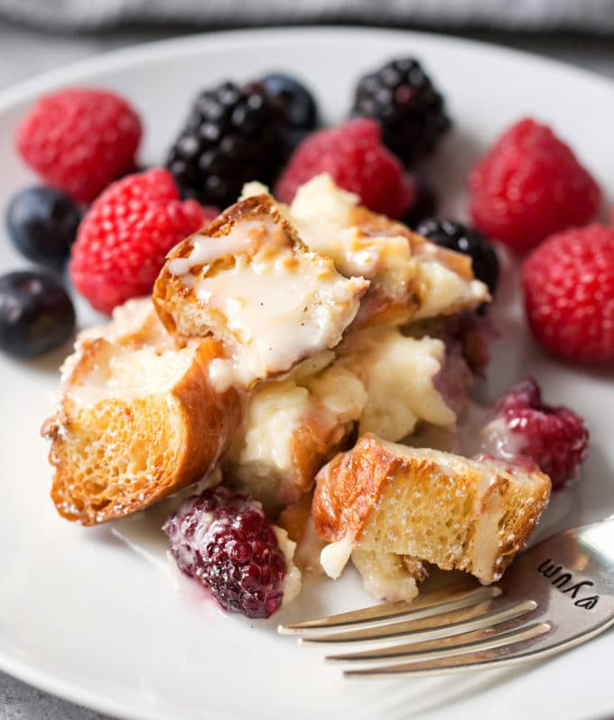 Sweet croissant breakfast casserole on plate with vanilla glaze