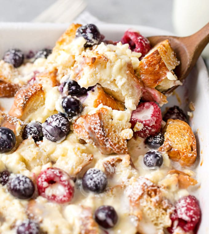 Scooping out a serving of croissant breakfast bake with berries