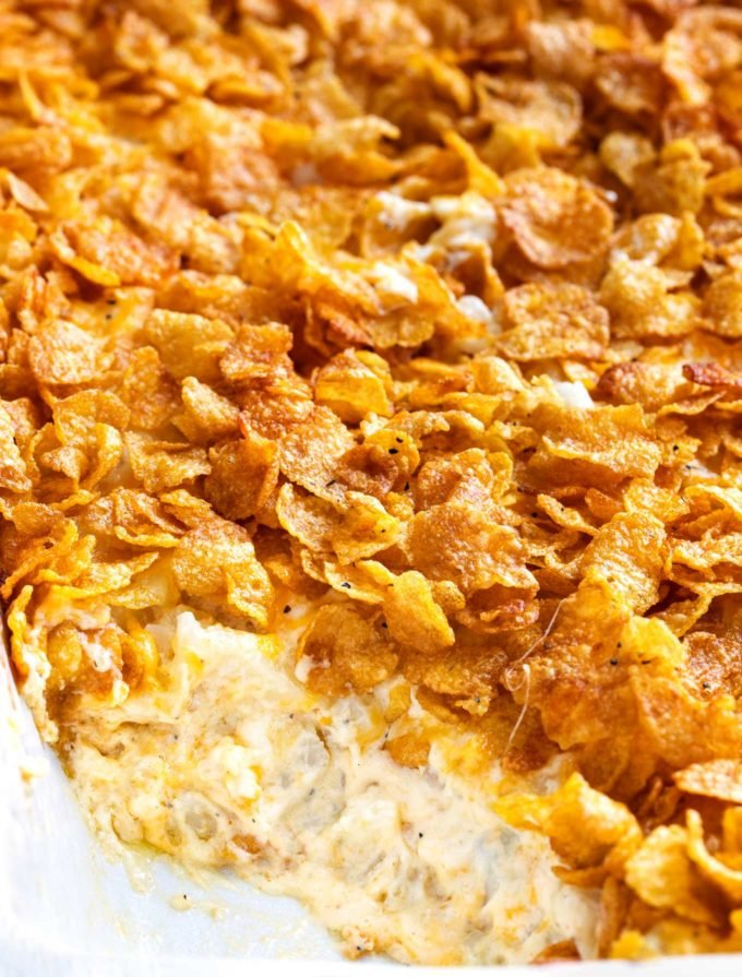 Funeral potatoes in white baking dish with scoop out