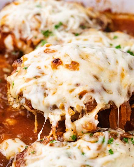 Juicy chicken breasts absolutely smothered in saucy caramelized onions and loads of gooey cheese!  French onion baked chicken is easy to prep ahead too! #bakedchicken #frenchonion #chicken #comfortfood #dinnerrecipe #easyrecipe